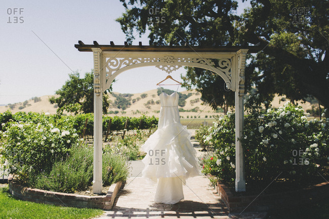 Bridal gown hanging outside from wooden hanger under wedding ceremony arch on sunny day