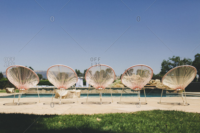 Five empty matching modern poolside chairs on sunny day