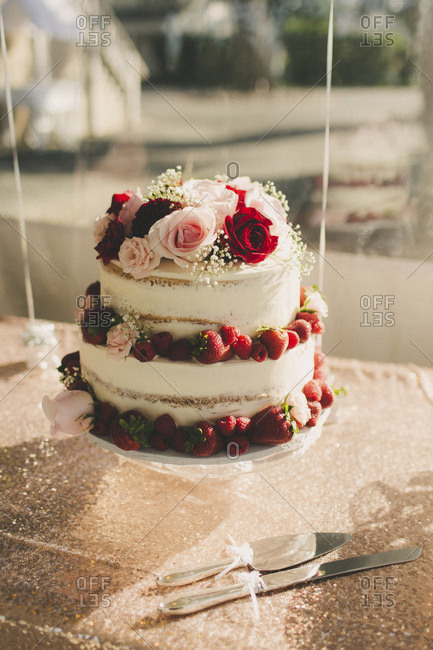 Three tiered weeding cake with roses and berries on shimmery tablecloth