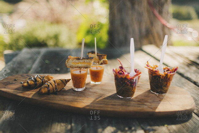 Assorted single serving wedding party refreshments on wood tray outside