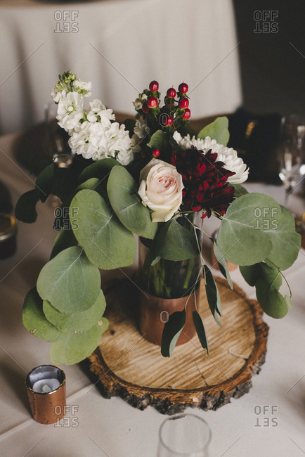 Wedding  floral centerpiece with wood and copper on dining table
