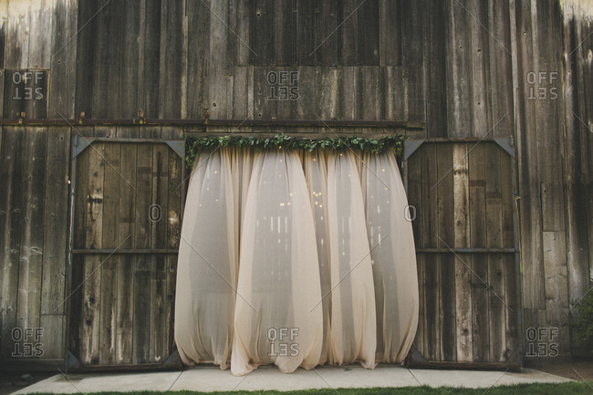 Wedding reception venue exterior wall with rustic barn doorway and sheer curtains