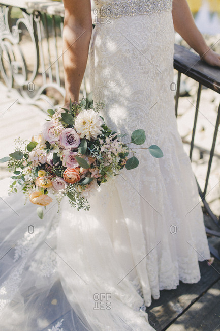 Bouquet and lower bridal gown close-up outside on wooden bridge
