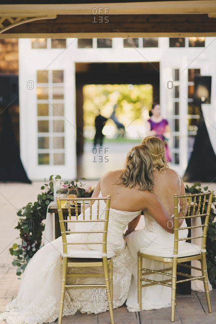 Blonde brides sitting close together at wedding reception table