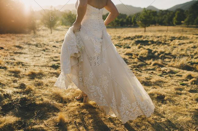 Bride walking through golden pasture in wedding dress