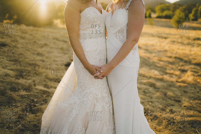 Brides standing in front of country sunset hand-in-hand