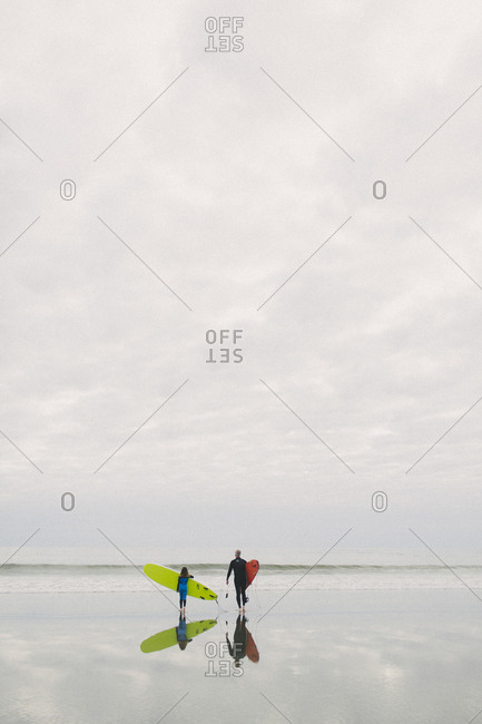 Younger girl and older male family surfers walking towards ocean