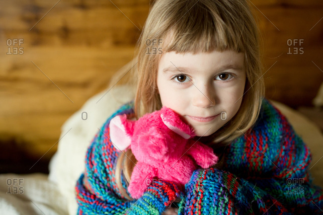 Little girl contentedly holding small elephant plush toy in corner of bedroom alone