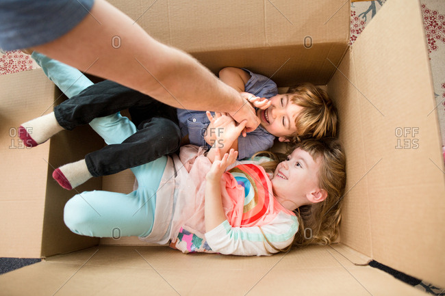 Parent reaching down to tickle brother and sister hiding ion cardboard box in the house