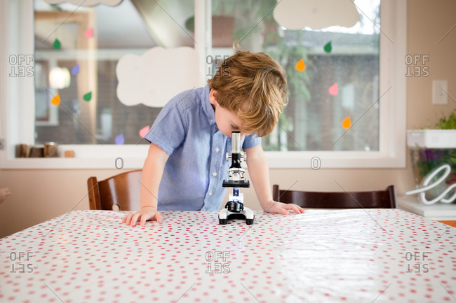 Cute aspiring scientist preschooler looking through microscope on school table