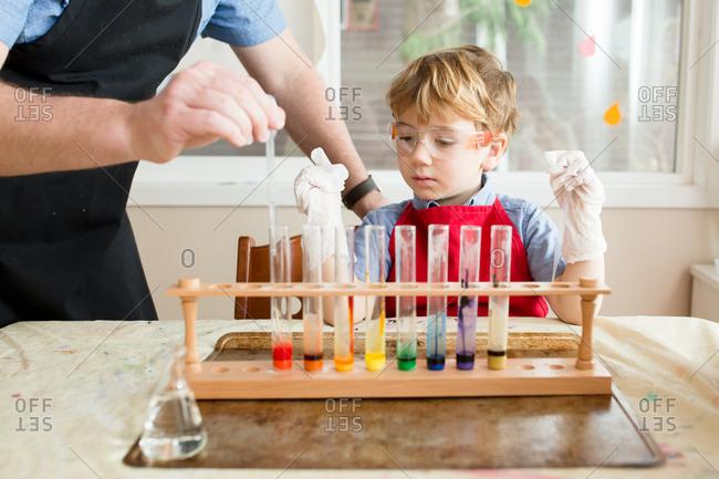 Little boy watches dad transfer liquid in toy chemistry set