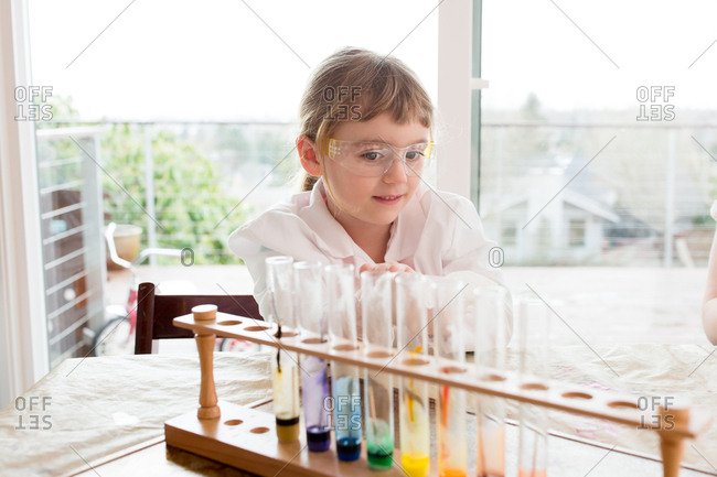 Girl in lab coat watching over science experiment results
