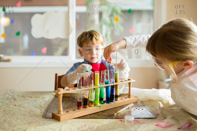 Studious siblings playing with chemistry set at the dining room table