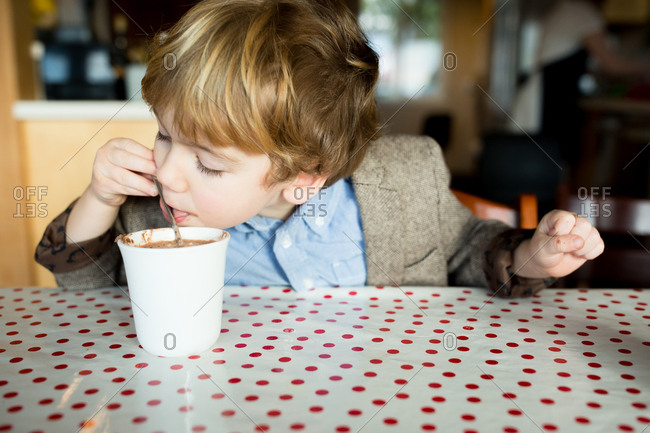 Little boy trying to lick hot cocoa drops off spoon in suit jacket