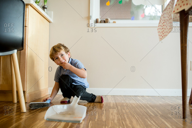 Coy toddler attempting to help sweep up wooden floor