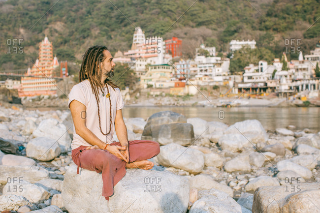 Man with dreadlocks watching river and sitting peaceful