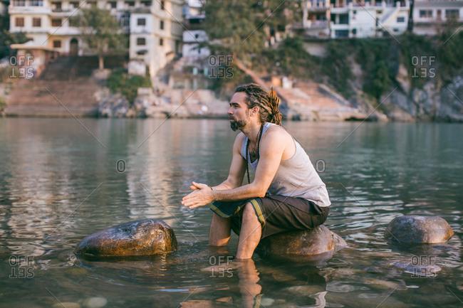 Man sitting on wet river rocks by himself