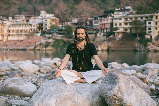 Traveler dedicated to meditation ritual on vacation at lake