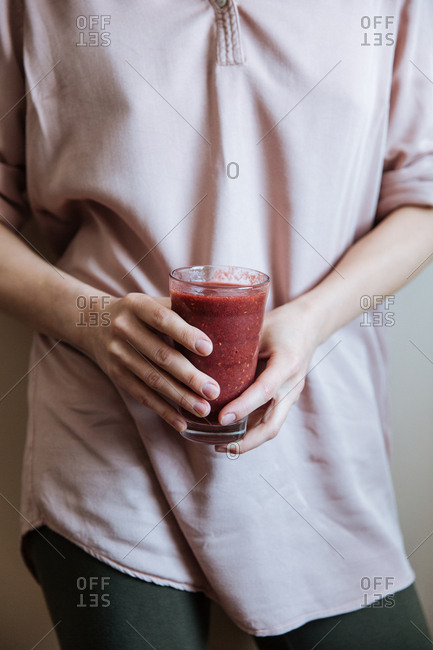 Woman holding homemade fruit smoothie in kitchen