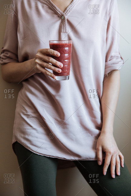 Lower half of woman leaning against interior wall with fresh smoothie