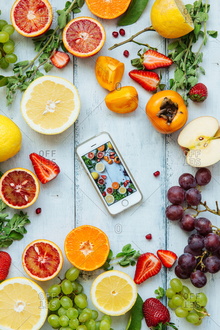 Smartphone set in middle of vibrant produce arranged for promotional imagery on table
