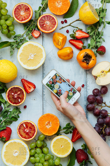 Fruits and vegetables arranged on wooden backdrop for smartphone photo shoot