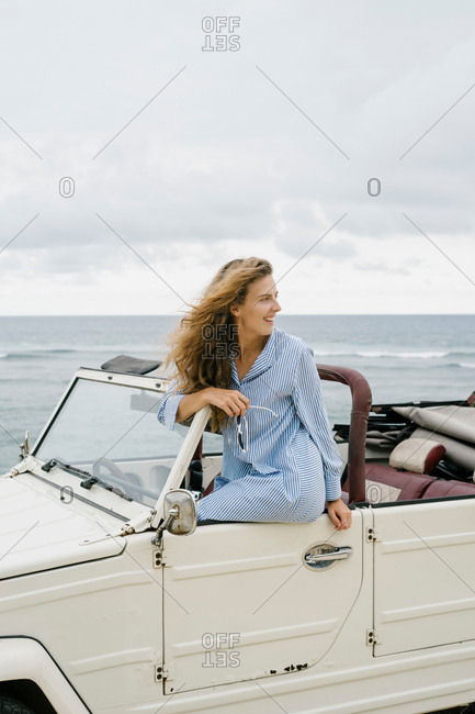 Happy woman sitting on door of convertible car with sea in background in Bali, Indonesia