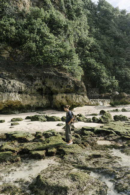 Woman exploring rock formations at low tide beach in Bali, Indonesia