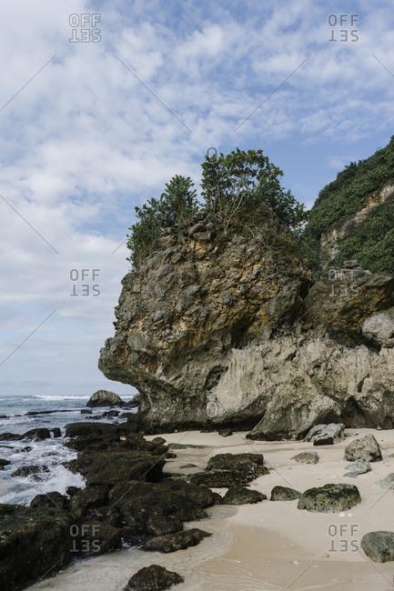 Rocky outcrop rising above beach in Bali, Indonesia