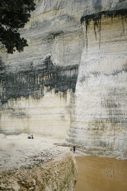 Bali, Indonesia - 29 November, 2017: Man dwarfed by limestone wall taking photo with smart phone in Bali, Indonesia