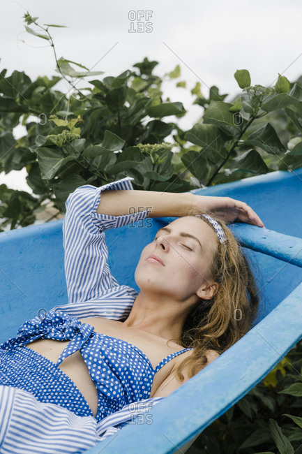 young woman wearing vintage swim wear lying in boat in Bali, Indonesia