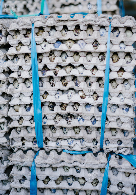 Large number of quails eggs in cartons stacked on top of one another in market in Bali, Indonesia