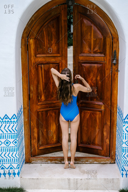 Rearview of woman in swim suit in front of entry gate to villa in Bali, Indonesia