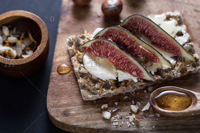 Fresh figs and cheese on whole grain cracker served with honey and chopped hazelnuts