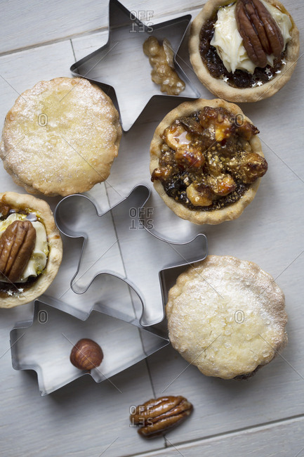 Christmas cookie cutters with homemade mini pies topped with nuts