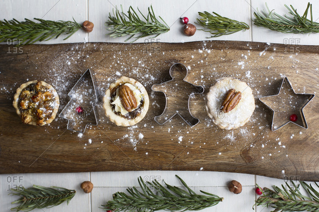 Mini pies topped with nuts and dusted with powdered sugar with Christmas cookie cutters