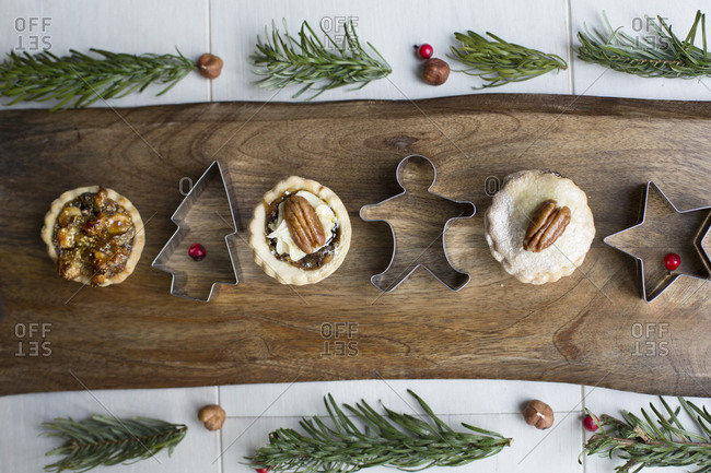 Mini pies topped with nuts served on wooden board with Christmas cookie cutters