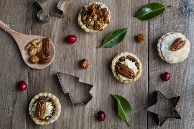 Mini pies served with nuts alongside Christmas cookie cutters