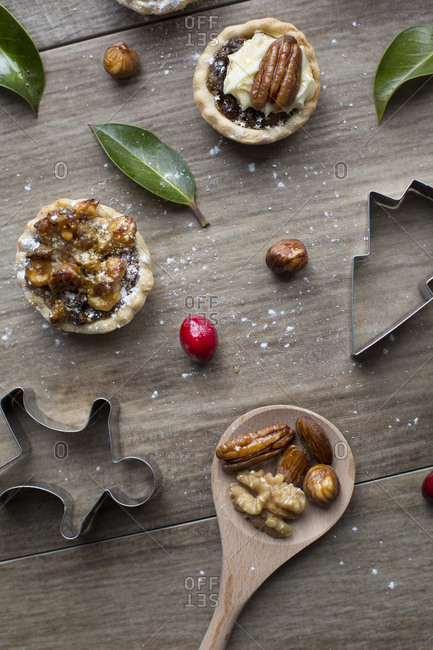 Homemade pies served with fresh whole nuts alongside Christmas cookie cutters
