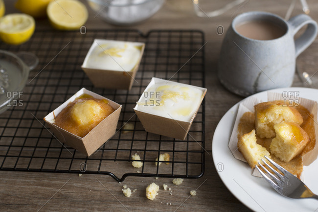 Freshly baked mini cakes in small containers served with hot beverage