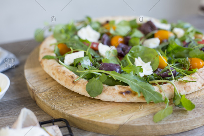Homemade pizza topped with fresh greens, olives, and tomatoes