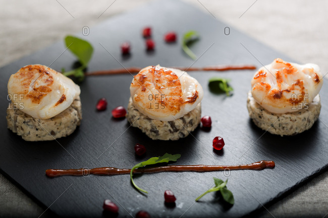 Seared scallops served on plate garnished with pomegranate seeds and sauce