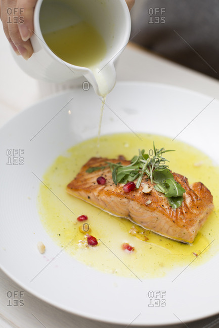 Person pouring olive oil on salmon fillet