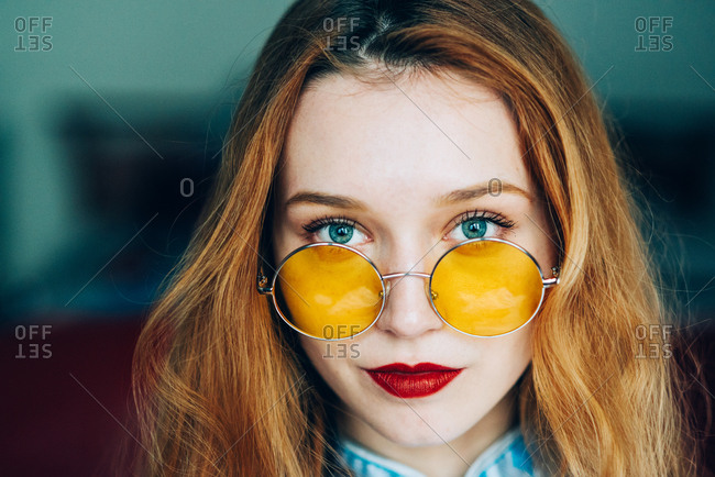 Portrait of beautiful red hair girl wearing retro glasses and wearing blue chinese dress
