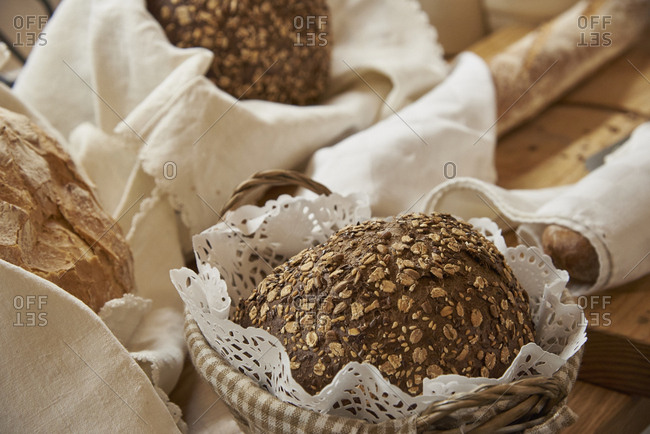 Selection of fresh baked loaves of bread including rustic whole wheat oat boule