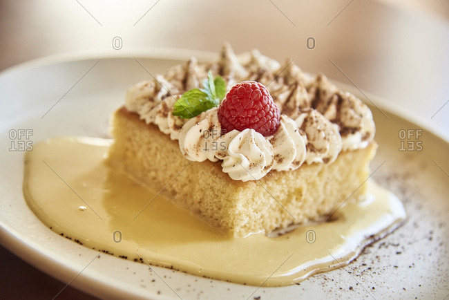 High angle view of slice of sponge cake with whipped cream and custard