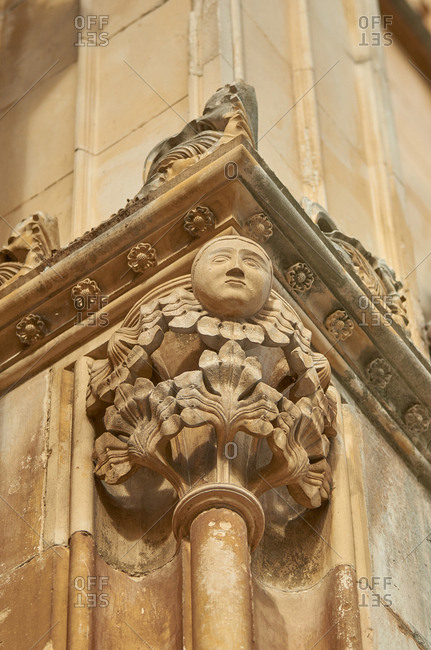 Detail of carved figurine on gothic facade of Batalha Monastery in Portugal