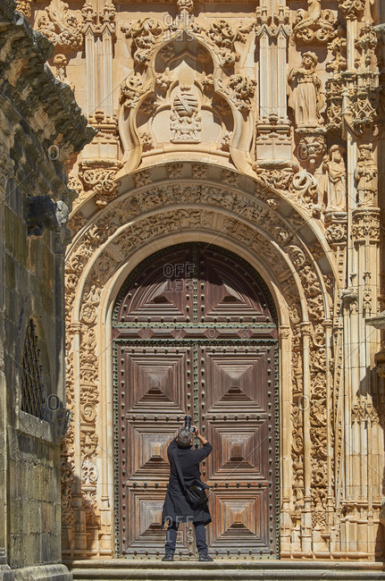 Rearview of tourist taking photograph of carvings on archivolt in an entryway to Batalha Monastery in Portugal