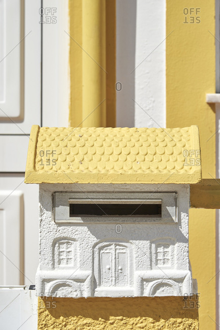 Detail of a mailbox in the shape of a house outside front door