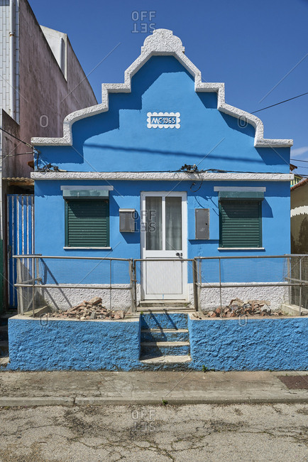 Facade of blue detached house with ornate eaves